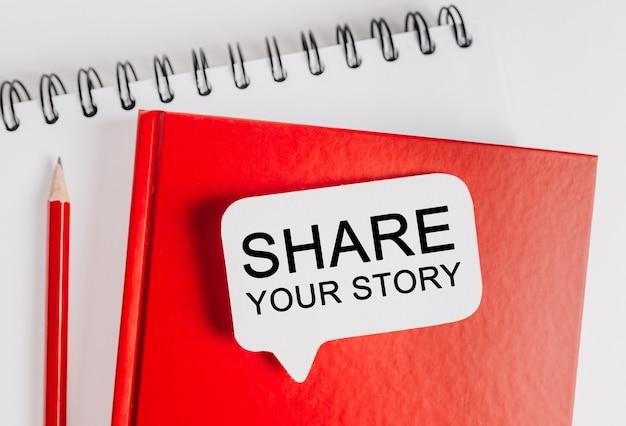 Testo condividi la tua storia su un adesivo bianco sul blocco note rosso con cancelleria per ufficio
