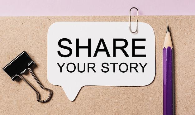 Testo condividi la tua storia su un adesivo bianco con sfondo di cancelleria per ufficio. lay piatto sul concetto di affari, finanza e sviluppo