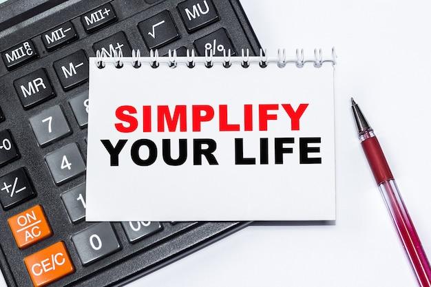 Testo semplifica la tua vita su taccuino, calcolatrice su sfondo bianco.