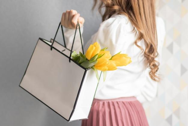 Testo vendita di primavera sul lightbox con borsa presente e bellissimi fiori su sfondo pastello. vendita festiva e banner promozionale.