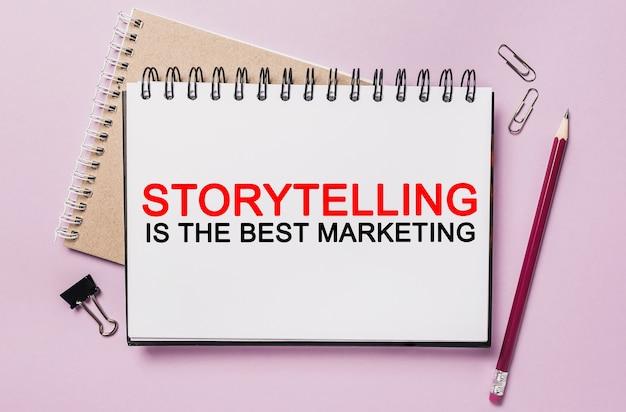 Text storytelling è il miglior marketing su un blocco note bianco con sfondo di cancelleria per ufficio. piatto disteso sul concetto di business, finanza e sviluppo