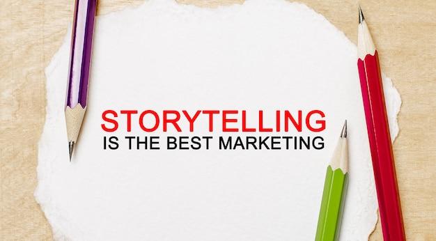 Text storytelling è il miglior marketing su un blocco note bianco con matite su uno spazio di legno