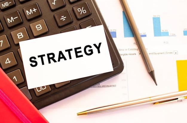 Strategia del testo su carta bianca con penna in metallo, calcolatrice e grafici finanziari.
