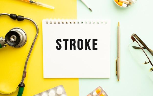 Tratto di testo su notebook con stetoscopio e penna su sfondo giallo. concetto medico.