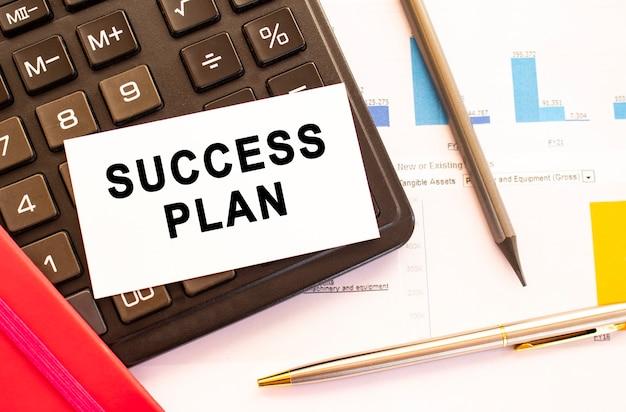 Piano di successo del testo su carta bianca con penna in metallo, calcolatrice e grafici finanziari.