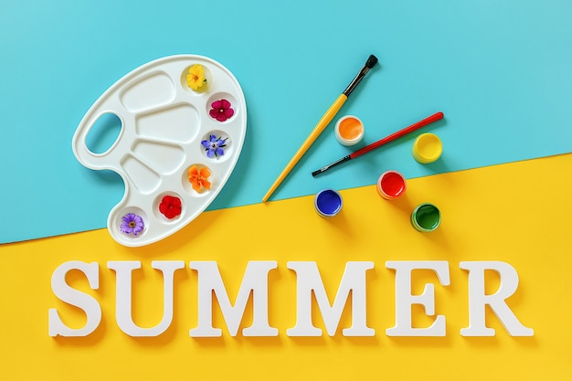 Testo estate, fiori colorati luminosi sulla tavolozza dell'artista, pennello e tempera su sfondo giallo blu. vernice di colori estivi concept creativo. vista dall'alto modello piatto laico per invito a cartolina di design.
