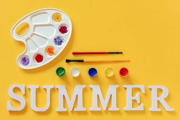 Testo estate, fiori colorati luminosi su tavolozza artistica, pennello e tempera su sfondo giallo. vernice di colori estivi concept creativo. vista dall'alto spazio per la copia piatta.