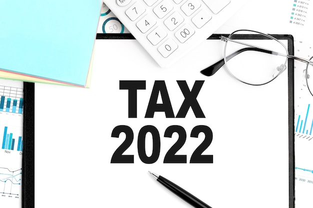 Testo tax 2022 su appunti, penna, occhiali, calcolatrice, adesivo, grafico. concetto di affari. disposizione piatta.