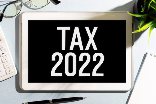 Testo tax 2022 su tablet, calcolatrice, occhiali, blocco note. concetto di contabilità. disposizione piatta.