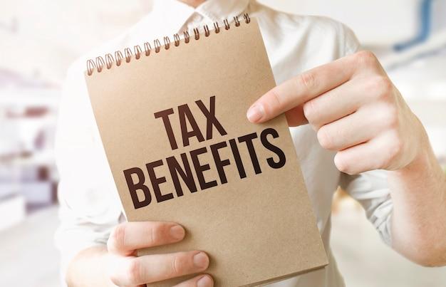 Testo benefici fiscali sul blocco note di carta marrone nelle mani dell'uomo d'affari in ufficio. concetto di affari Foto Premium
