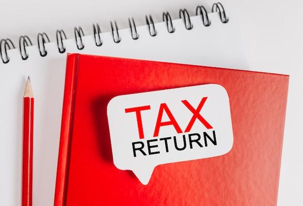 Testo dichiarazione dei redditi su un adesivo bianco sul blocco note rosso con sfondo di cancelleria per ufficio. lay piatto sul concetto di affari, finanza e sviluppo