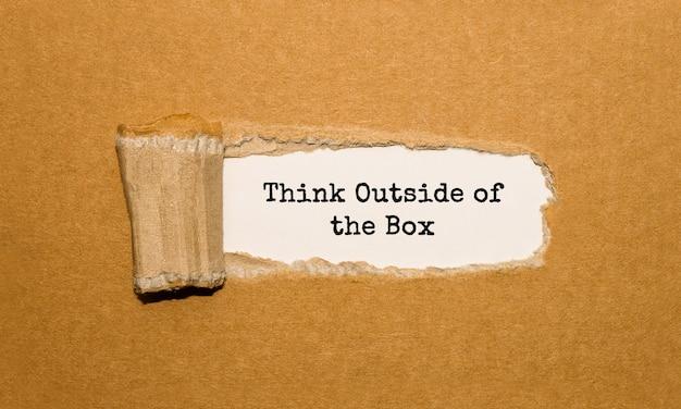 Il testo think outside of the box appare dietro carta marrone strappata