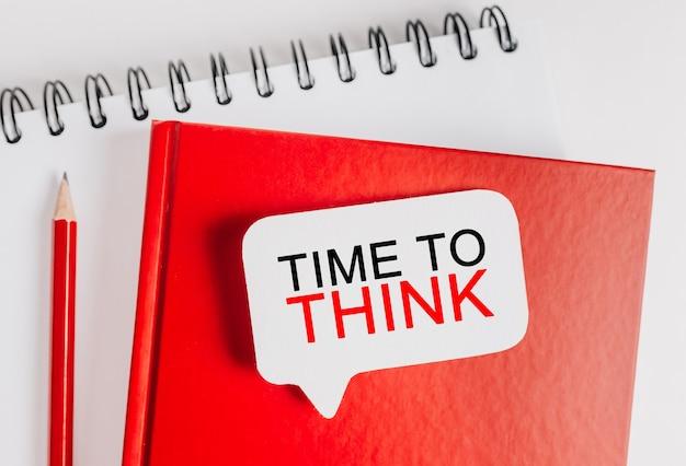 Testo time to think su un adesivo bianco sul blocco note rosso con spazio di cancelleria per ufficio