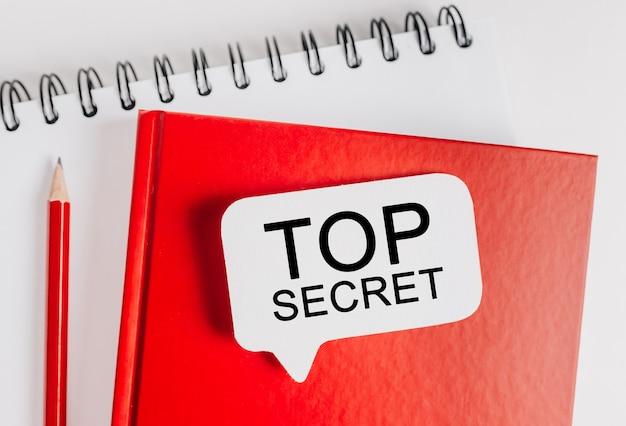Testo top secret su un adesivo bianco sul blocco note rosso con spazio di cancelleria per ufficio