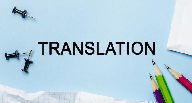 Traduzione del testo su un blocco note bianco con matite su sfondo blu