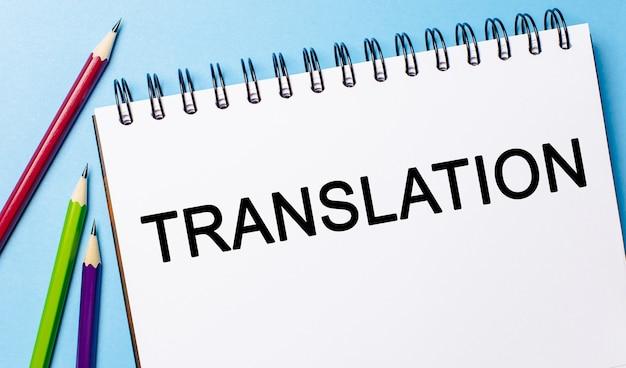 Traduzione del testo su un blocco note bianco con le matite su uno spazio blu