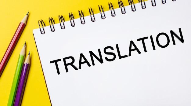 Traduzione del testo su un blocco note bianco con matite su uno sfondo giallo. concetto di affari