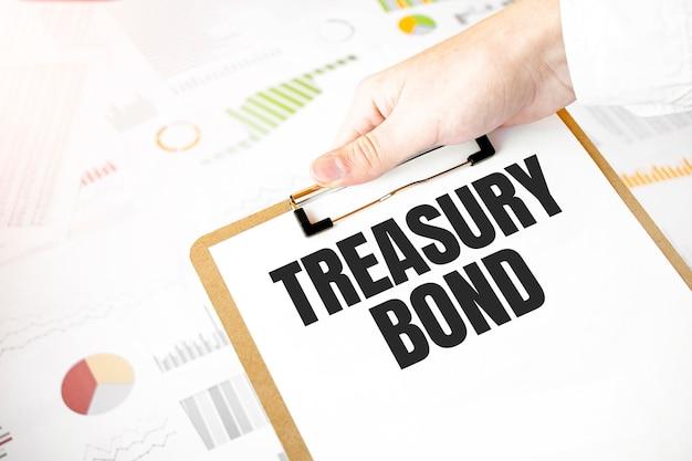Testo buoni del tesoro sul piatto di carta bianca nelle mani di uomo d'affari con diagramma finanziario.