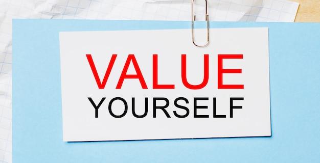 Il testo valuta te stesso su una carta bianca su sfondo blu. concetto di affari