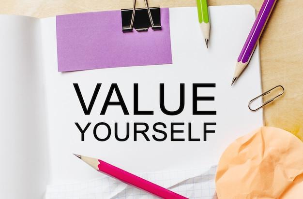 Testo valorizza te stesso su uno spazio bianco per note con matite, adesivi e graffette