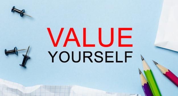 Testo valorizza te stesso su un blocco note bianco con matite su uno spazio blu