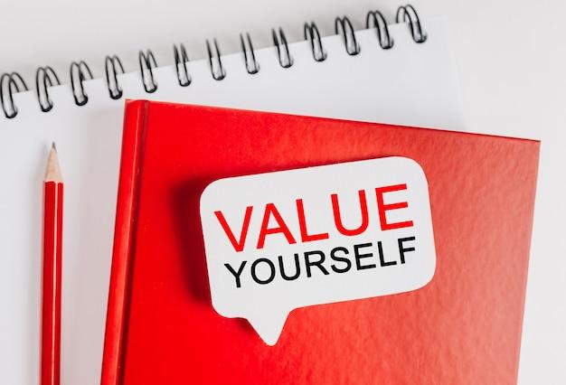 Testo valorizza te stesso su un adesivo bianco sul blocco note rosso con cancelleria per ufficio