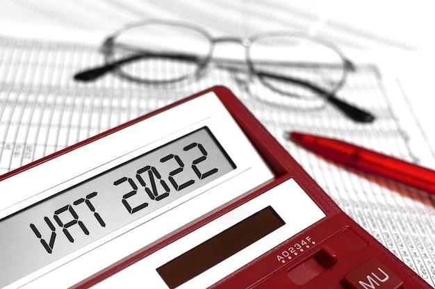 Testo iva 2022 - imposta sul valore aggiunto su calcolatrice, occhiali, penna. disposizione piana di affari.
