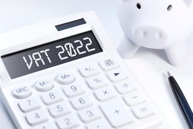 Testo iva 2022 - valore - imposta aggiunta su calcolatrice, laptop, chat, grafici. disposizione piana di affari.