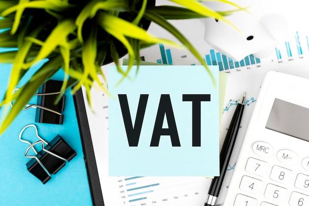 Testo iva - imposta sul valore aggiunto su adesivo blu, calcolatrice, penna, maialino, grafici, pianta. disposizione piana di affari.