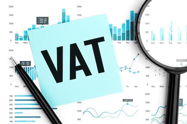 Testo iva - imposta sul valore aggiunto su adesivo blu, lente d'ingrandimento, penna, grafici. disposizione piana di affari.