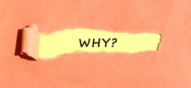 Il testo why che appare su carta gialla dietro carta colorata strappata. vista dall'alto.