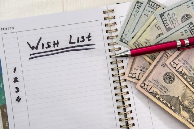 Lista dei desideri di testo sul blocco note con banconote da un dollaro. pianificare per il futuro