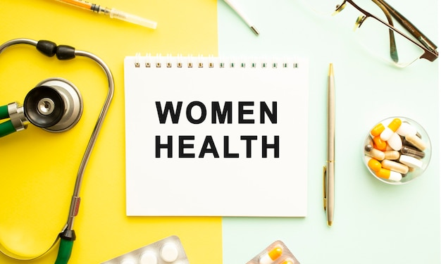 Testo salute delle donne sul taccuino con lo stetoscopio e la penna