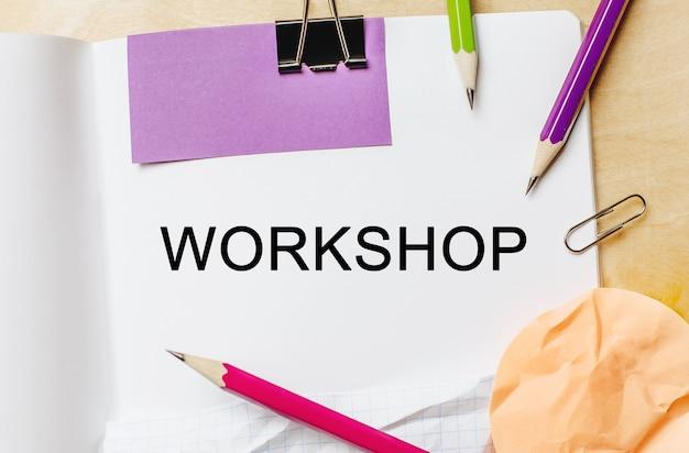 Workshop di testo su uno spazio bianco per note con matite, adesivi e graffette