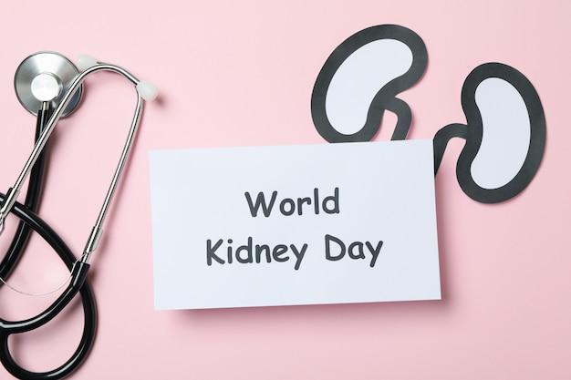 Testo giornata mondiale del rene, reni di carta e stetoscopio sul rosa
