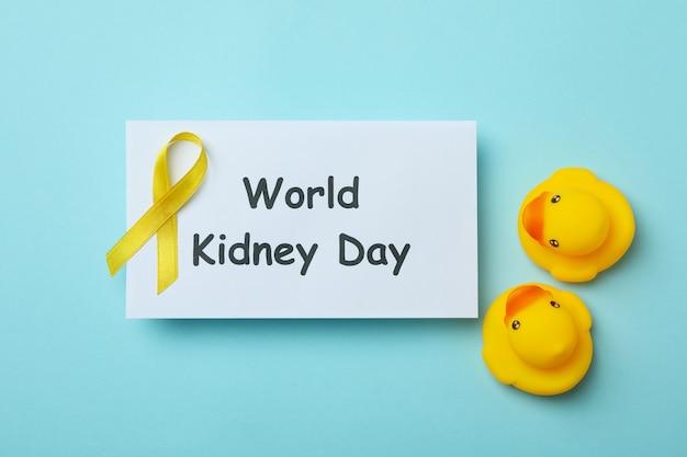 Testo giornata mondiale del rene, nastro giallo di consapevolezza e papere di gomma su sfondo blu