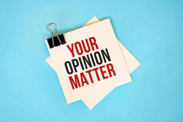 Scrivi la tua opinione su foglietti adesivi con copia spazio e graffetta