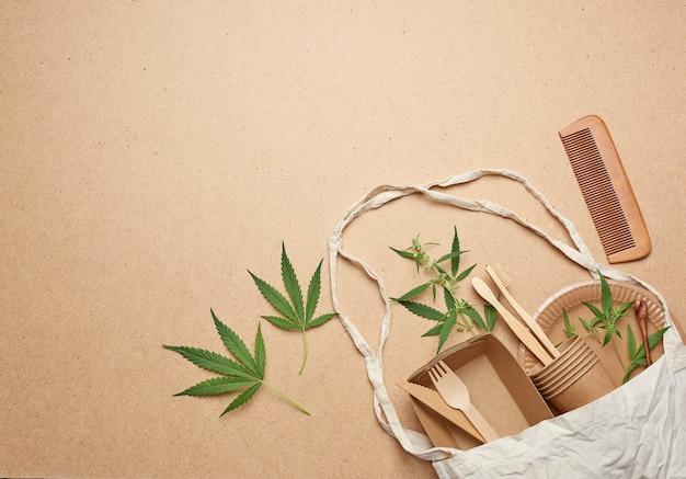 Borsa in tessuto e stoviglie usa e getta da carta artigianale marrone, foglie di canapa verde su un legno