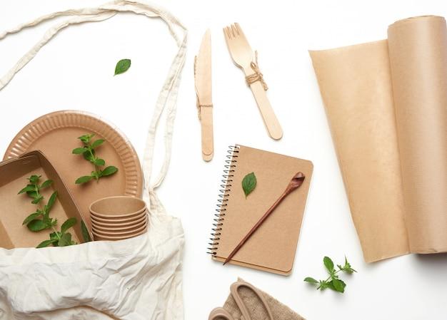 Borsa in tessuto e stoviglie usa e getta da carta artigianale marrone, foglie di menta verde su fondo bianco