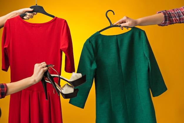 Concetto di moda di abbigliamento di design tessile le mani femminili con abiti in mano su giallo