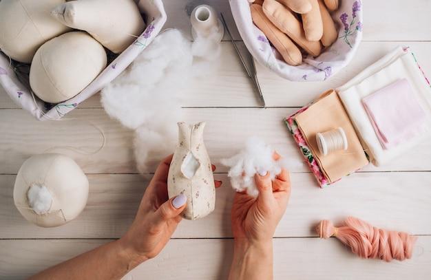Bambola tessile nel processo di cucito con accessori e materiali