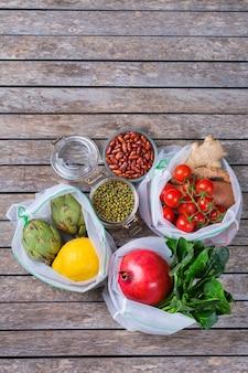 Borsa in rete tessile con prodotti, frutta e verdura. zero sprechi, eco-compatibile, senza plastica, riciclato, riutilizzabile, concetto di spesa sostenibile. copia spazio, sfondo piatto