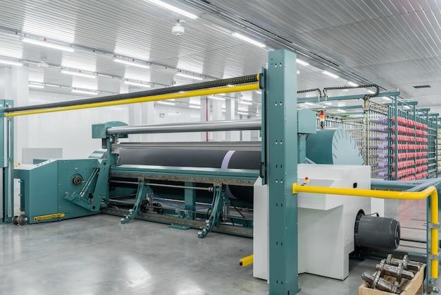 Il filato tessile sulla macchina avvolgitrice è avvitato sul grande albero attrezzatura in una fabbrica tessile
