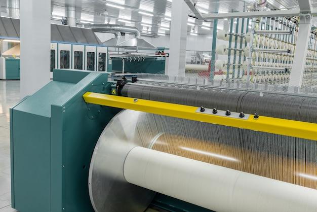 Il filato tessile sulla macchina avvolgitrice è avvitato sull'attrezzatura dell'albero grande in una fabbrica tessile