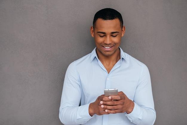 Sms ad un amico. fiducioso giovane africano guardando il suo smartphone e sorridendo