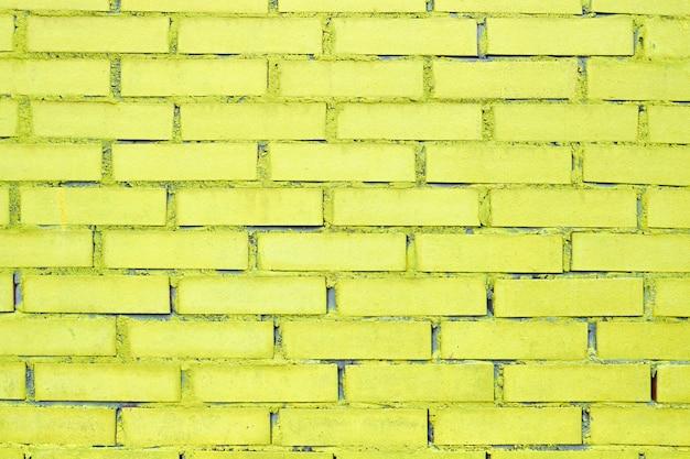 Struttura e fondo del mattone con pittura gialla.