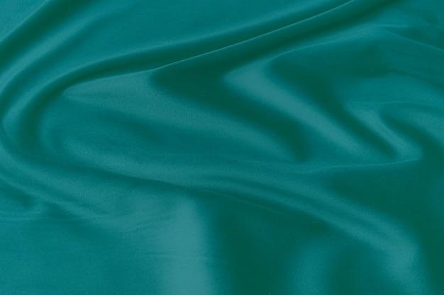 Trama, sfondo, motivo. trama di tessuto di seta verde. bellissimo tessuto di seta morbida verde smeraldo.