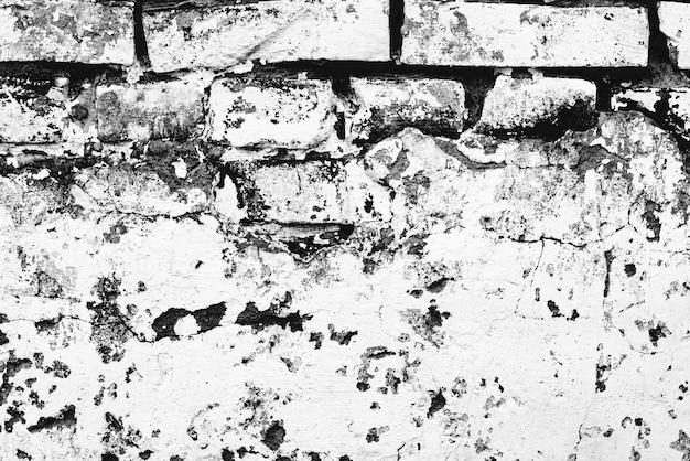 Texture di un muro di mattoni con crepe e graffi sullo sfondo