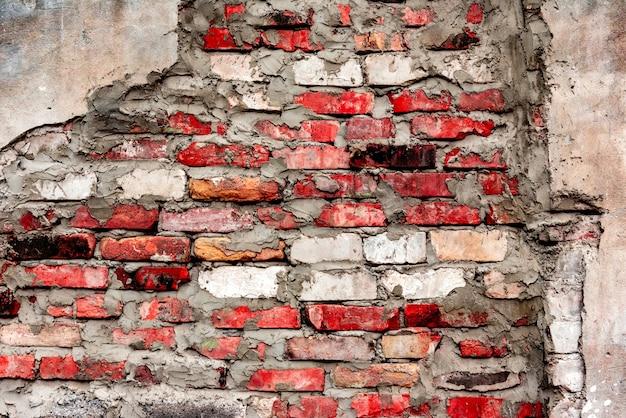 Trama di un muro di mattoni con crepe e graffi