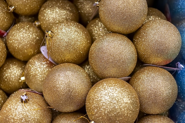 Trama di palline lucide dorate di natale. decorazione di natale per il nuovo anno e natale. avvicinamento. focalizzazione morbida